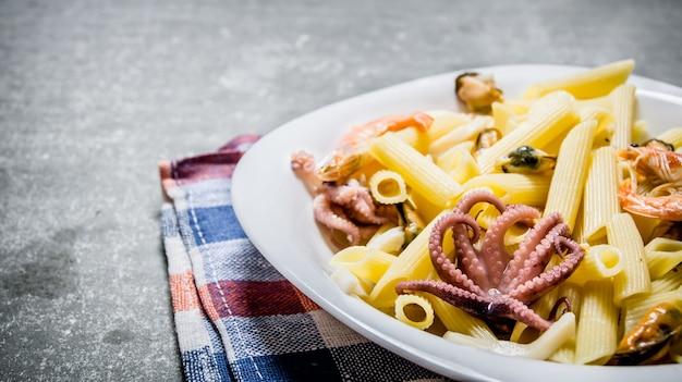 Pasta met zeevruchten op een plaat op de stof op de stenen tafel Premium Foto