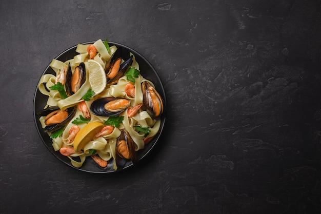 Pasta met zeevruchten op stenen tafel. mosselen en garnalen. bovenaanzicht met kopie ruimte.