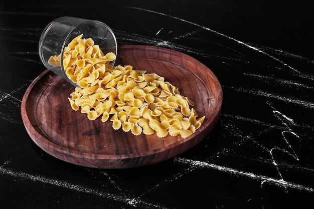 Pasta op een houten schotel uit een glazen beker