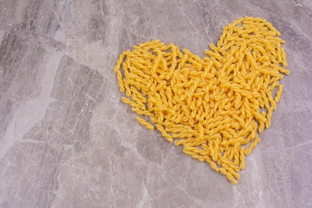 Pasta op een marmeren ondergrond in hartvorm