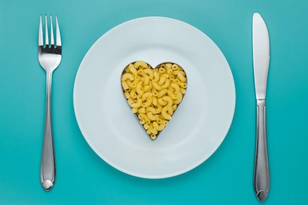 Pasta op een witte plaat met vork en mes
