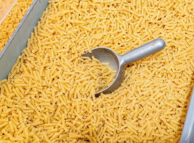 Pasta op gewicht in een supermarkt, deegproducten op een toonbank, verse pasta op gewicht