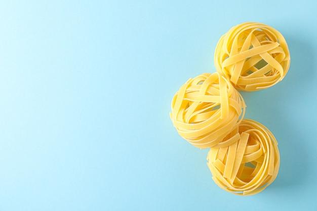 Pasta op kleur achtergrond, ruimte voor tekst. droge rauwe hele pasta
