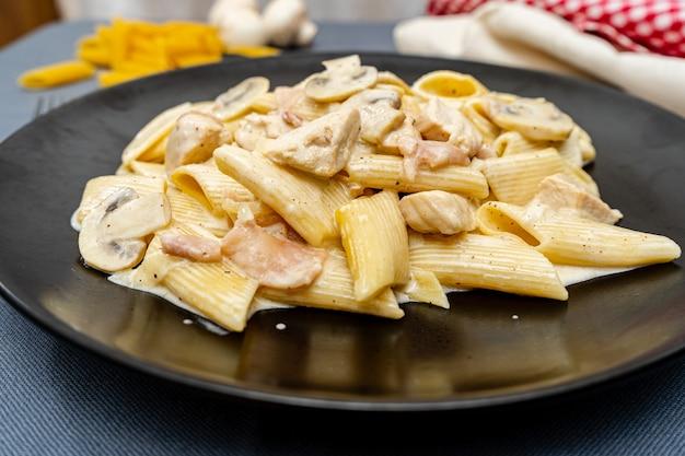 Pasta penne met jam, kip en champignon onder parmezaanse kaas