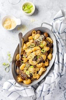 Pasta pipa rigate en champignons champignon gebakken in sojasaus, met peper, parmezaanse kaas en gestoomde uien in een oude metalen kom op een oude vintage tafel. selectieve focus