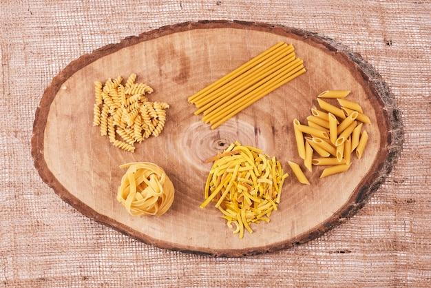 Pasta rassen op een houten bord, bovenaanzicht.
