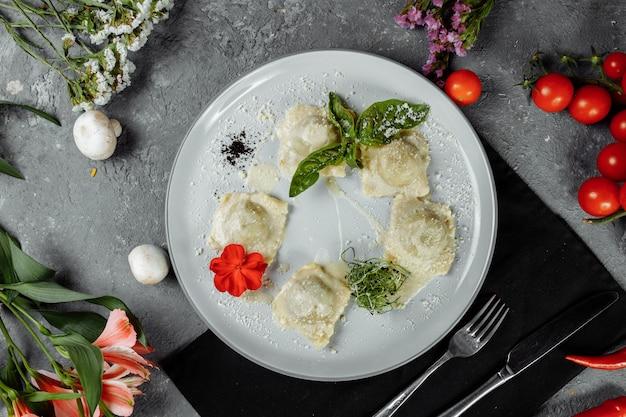 Pasta ravioli met vlees, tomaat en basilicum.