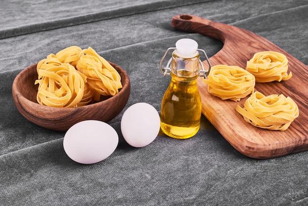 Pasta rolt in een houten schotel met groenten.