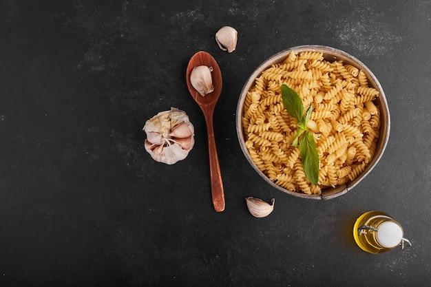 Pasta's in een metalen kom met ingrediënten eromheen.