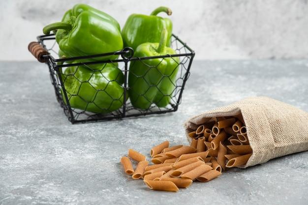 Pasta's in een rustieke zak met groene chilipepers eromheen.