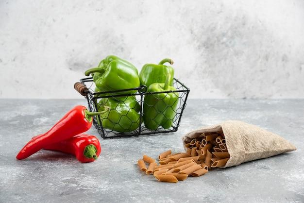 Pasta's in een rustieke zak met rode en groene chilipepers eromheen.