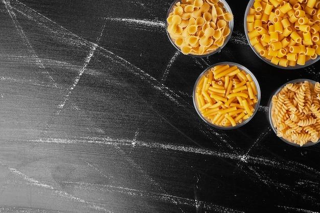Pasta's in glazen bekers in zwarte tafel.