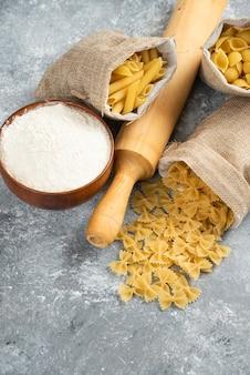 Pasta's in rustieke mand met deegroller en een houten kopje bloem rond.