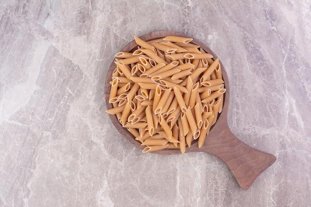 Pasta's op een houten schaal op de marmeren ruimte.