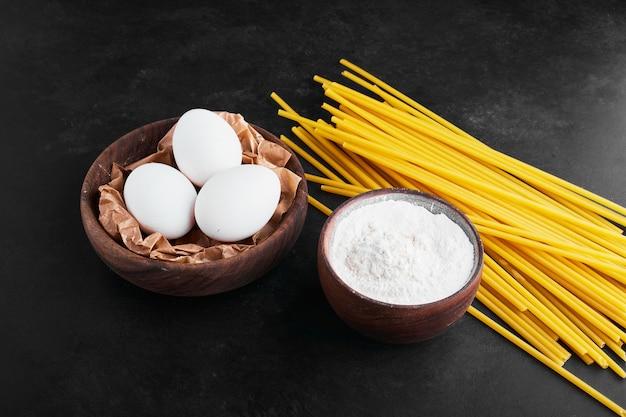 Pasta's op zwart met eieren en bloem.