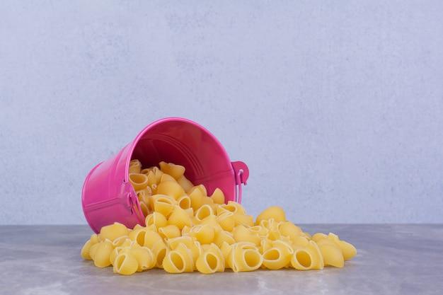 Pasta's uit een roze metalen emmer.