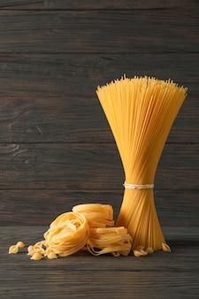 Pasta samenstelling op houten tafel, ruimte voor tekst. droge rauwe hele pasta