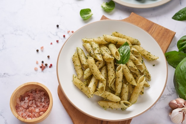 Pasta spaghetti met courgette, basilicum, room en kaas op stenen tafel.
