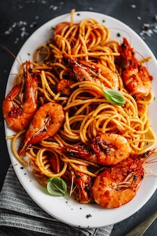 Pasta spaghetti met garnalen en tomatensaus geserveerd op plaat op donkere ondergrond. detailopname.