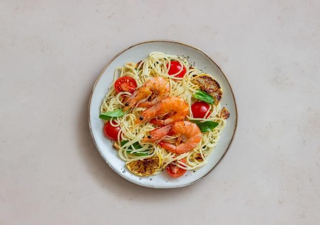 Pasta spaghetti met garnalen, tomaten, knoflook, spinazie en citroen. italiaanse keuken. zeevruchten. eetpatroon.