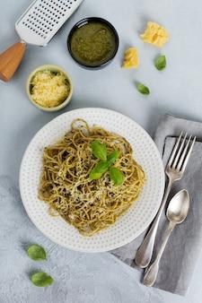 Pasta spaghetti met pestosaus, basilicum en parmezaanse kaas op een witte keramische plaat en grijze beton of stenen achtergrond. traditioneel italiaans gerecht.