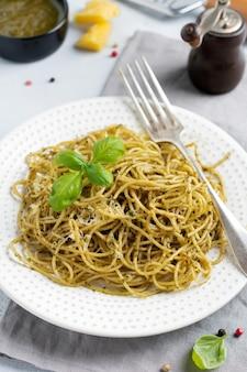 Pasta spaghetti met pestosaus, basilicum en parmezaanse kaas op een witte keramische plaat en grijze betonnen of stenen achtergrond. traditioneel italiaans gerecht. selectieve aandacht. bovenaanzicht.