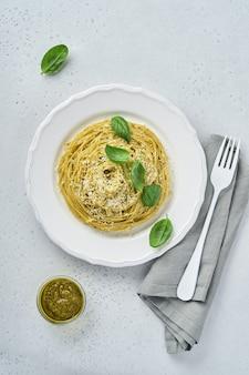 Pasta spaghetti met pestosaus en verse basilicum bladeren in witte kom. grijze achtergrond. bespotten. bovenaanzicht.