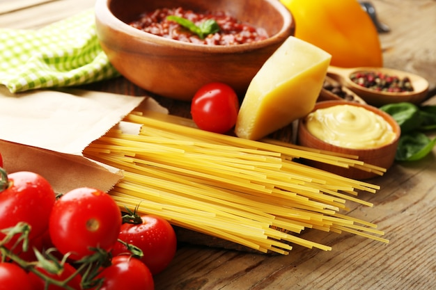 Pasta spaghetti met tomaten, saus bolognese, kaas en basilicum op rustieke houten achtergrond