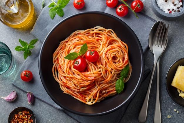 Pasta, spaghetti met tomatensaus in zwarte kom. bovenaanzicht