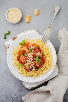 Pasta spaghetti met tomatensaus, parmezaanse kaas, basilicum en gehaktballen op witte keramische plaat op grijze betonnen ondergrond