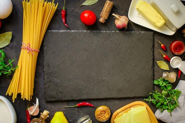 Pasta, spaghetti of bucatini en tomatensaus ingrediënten. voedsel achtergrond. kopie ruimte