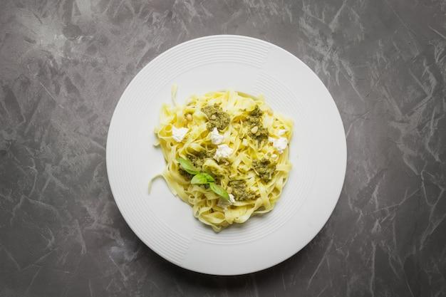 Pasta tagliatelle met pesto, pijnboompitten, roomkaas op grijs. heerlijke mediterrane lunch.