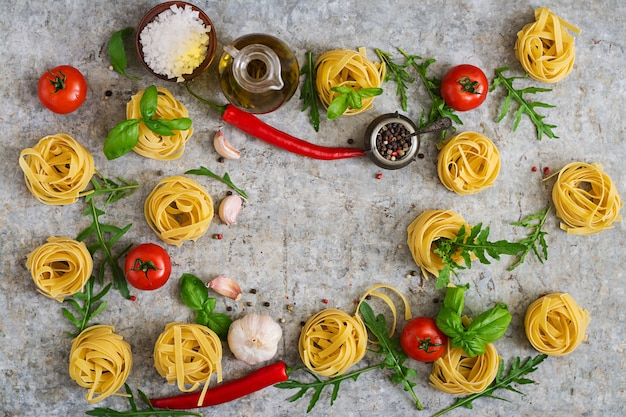 Pasta tagliatelle nest en ingrediënten voor het koken (tomaten, knoflook, basilicum, chili). bovenaanzicht
