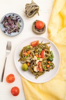 Pasta van de tagliatelle groene spinazie met tomaat, erwt en microgreen spruiten op een witte houten tafel en geel textiel. bovenaanzicht, plat leggen, close-up.