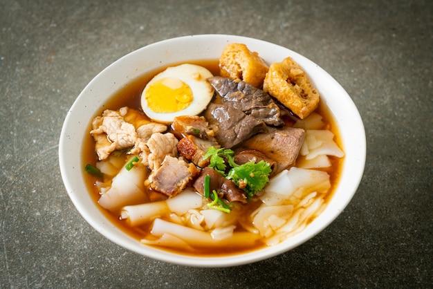 Pasta van rijstmeel of gekookt chinees pastavierkant met varkensvlees in bruine soep - aziatisch eten