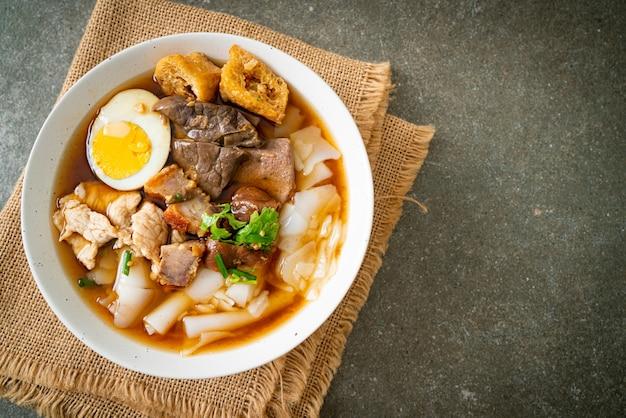 Pasta van rijstmeel of gekookt chinees pastavierkant met varkensvlees in bruine soep. aziatische eetstijl
