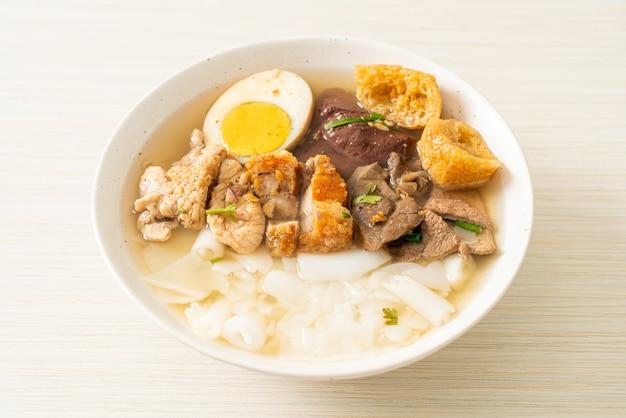 Pasta van rijstmeel of gekookt chinees pastavierkant met varkensvlees in heldere soep - aziatisch eten