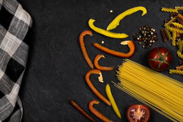 Pasta, verse, gesneden groenten, zwarte en witte handdoek liggend op zwarte achtergrond met ruimte voor tekst. bovenaanzicht.