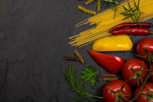 Pasta, verse groenten, rozemarijn liggen op een zwarte achtergrond met ruimte voor tekst. bovenaanzicht. voedsel achtergrond.