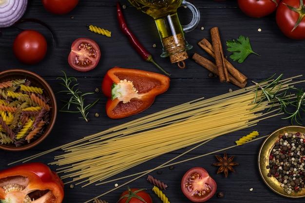 Pasta, verse tomaten, hete pepers, rozemarijn en dille, olijfolie op een zwarte achtergrond. bovenaanzicht.