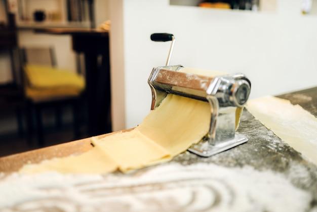 Pastamachine met deeg op houten keukentafel besprenkeld met bloem, niemand. traditionele italiaanse keuken