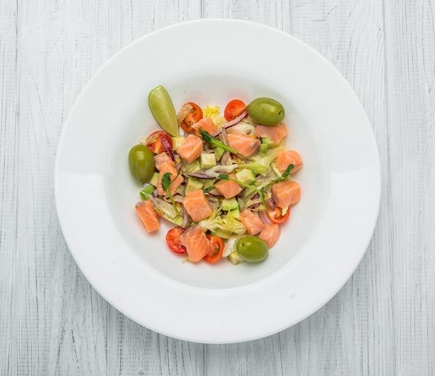 Pastasalade met gerookte zalm, olijven, cherrytomaatjes, roze peper en verse basilicum zelfgemaakte gerechten symbolisch beeld