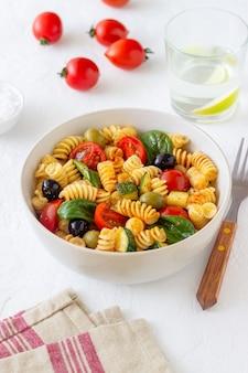 Pastasalade met tomaten, courgette, olijven en spinazie. gezond eten. vegetarisch eten.