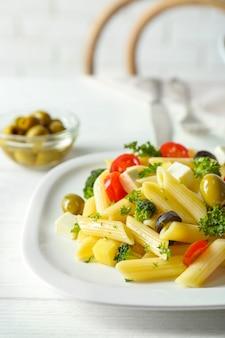 Pastasalade met tomaten en olijven op houten tafel