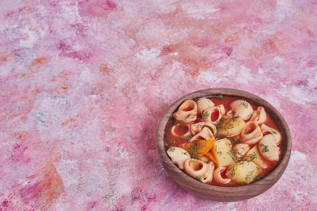 Pastasoep in tomatensaus in een houten beker.