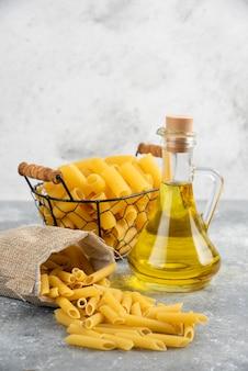 Pastasoorten in een metalen mand en rustieke zak met olijfolie op grijze tafel.