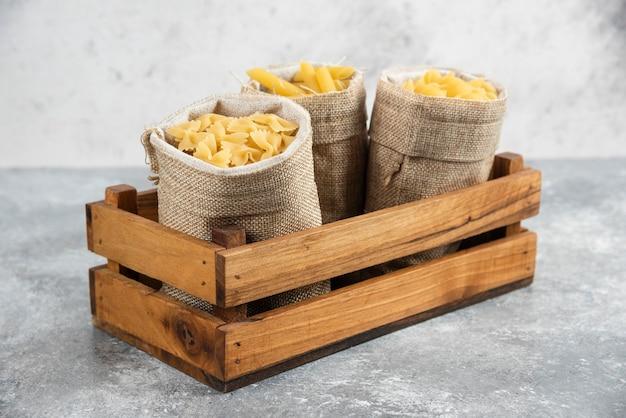 Pastasoorten in rustieke mand in een houten dienblad.