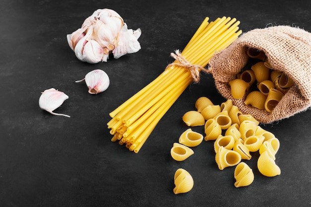 Pastasoorten op zwart met knoflookteentjes opzij.
