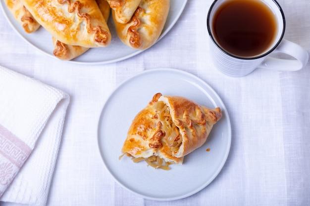 Pastei (pirozhki) met kool. zelfgemaakt bakken. traditionele russische en oekraïense keuken. op de achtergrond is een gerecht met taarten. detailopname.