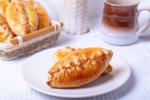 Pastei (pirozhki) met kool. zelfgemaakt bakken. traditionele russische en oekraïense keuken. op de achtergrond is een mand met taarten. detailopname.